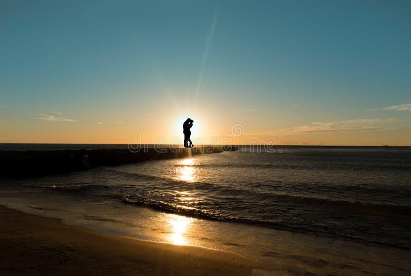 Silhouette d'un couple embrassant par la mer au lever de soleil photos libres de droits