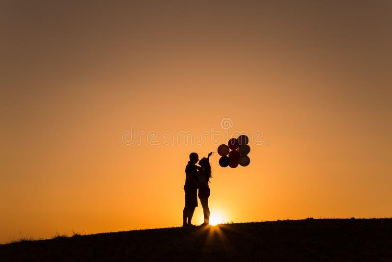 Silhouette d'un couple jouant avec des ballons au coucher du soleil photographie stock
