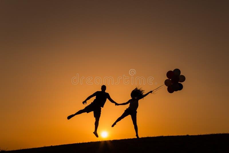 Silhouette d'un couple jouant avec des ballons au coucher du soleil photo libre de droits