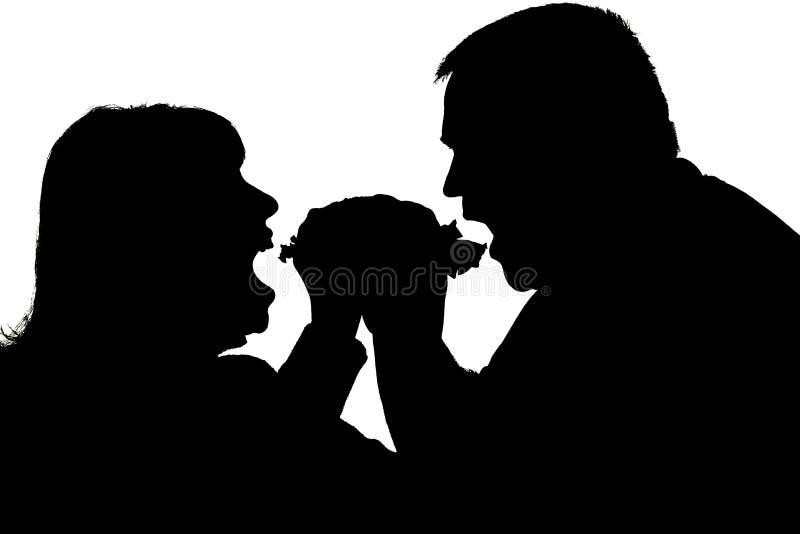 Silhouette d'un couple mangeant avec un appétit un hamburger photos stock
