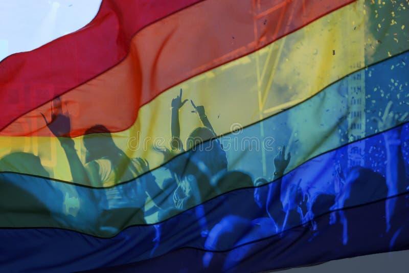 silhouette d'un défilé des gays et lesbiennes avec un drapeau d'arc-en-ciel - symbole de l'amour et de la tolérance images libres de droits
