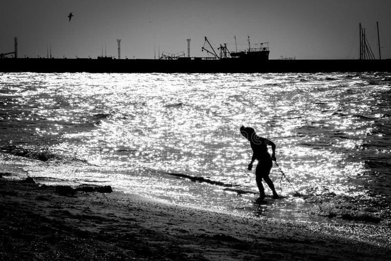 Silhouette d'un enfant émergeant de la mer à l'arrière-plan du port photo stock
