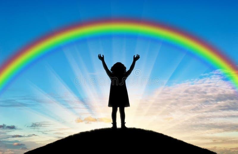 Silhouette d'un enfant heureux de petite fille avec les bras augmentés essayant de toucher l'arc-en-ciel photos stock