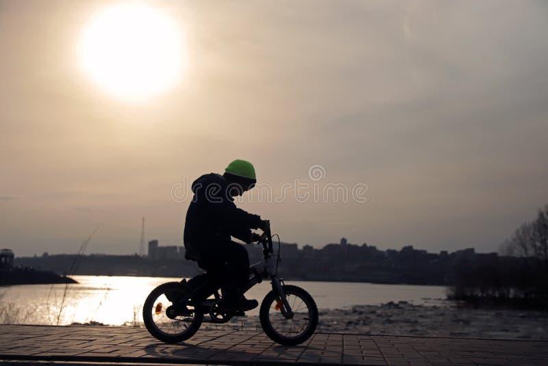 Silhouette d'un garçon montant une bicyclette en parc photographie stock