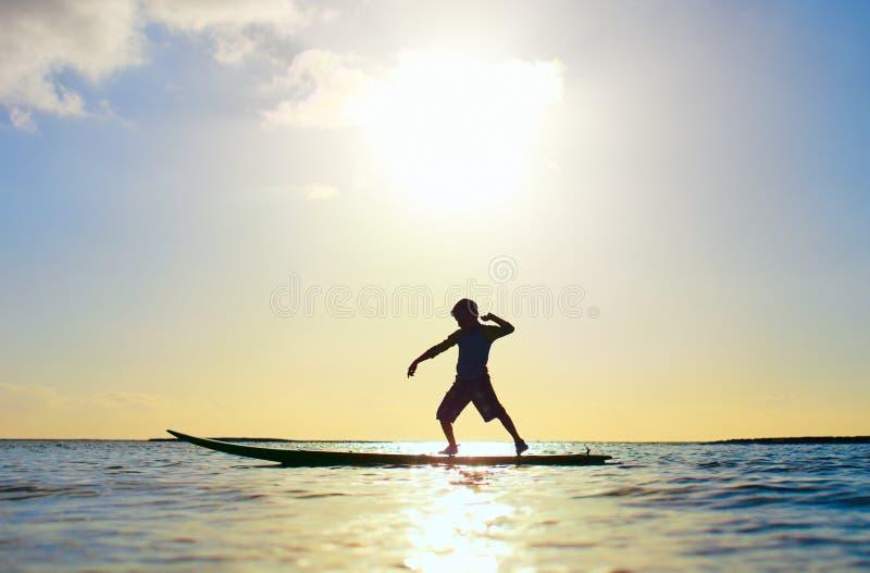 Silhouette d'un garçon sur la planche de surfing image stock
