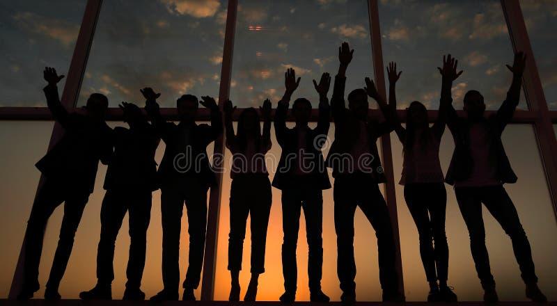 Silhouette d'un groupe de gens d'affaires soulevant leur main images libres de droits
