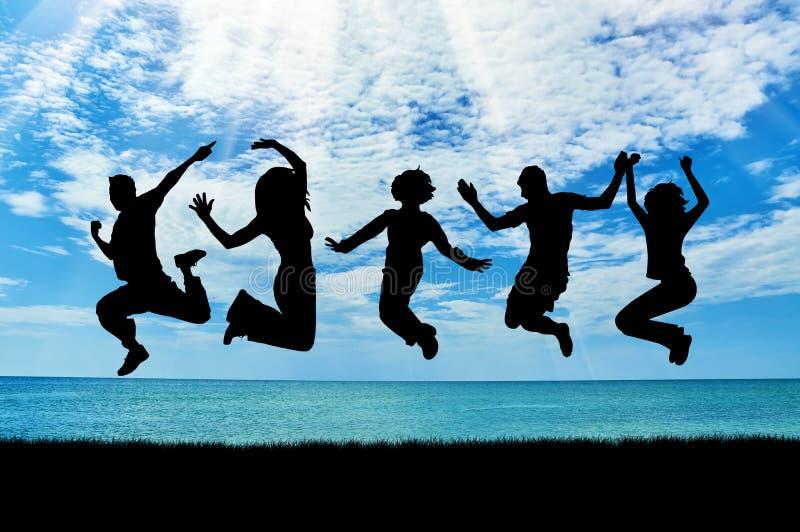 Silhouette d'un groupe de personnes heureux sauter image stock