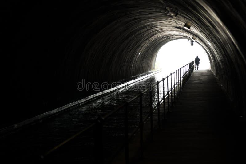 Silhouette d'un homme d'Appraching en Front Of Bright Light At l'extrémité d'un tunnel foncé image stock