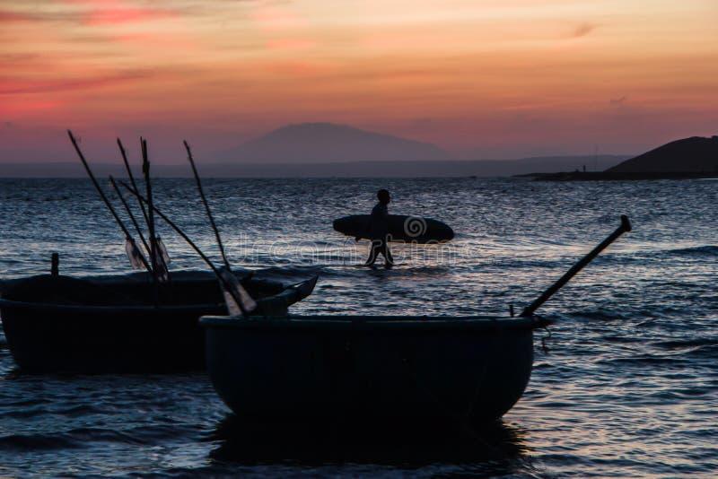 Silhouette d'un homme avec une planche de surf en mer au coucher du soleil images libres de droits