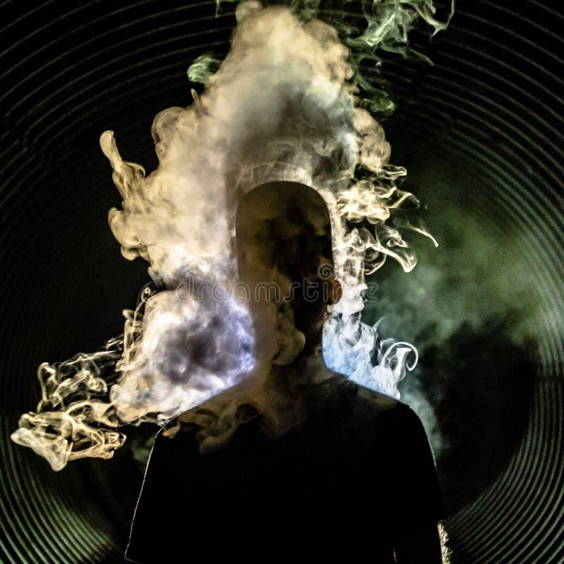 Silhouette d'un homme couvert dans la fumée de tourbillonnement image stock