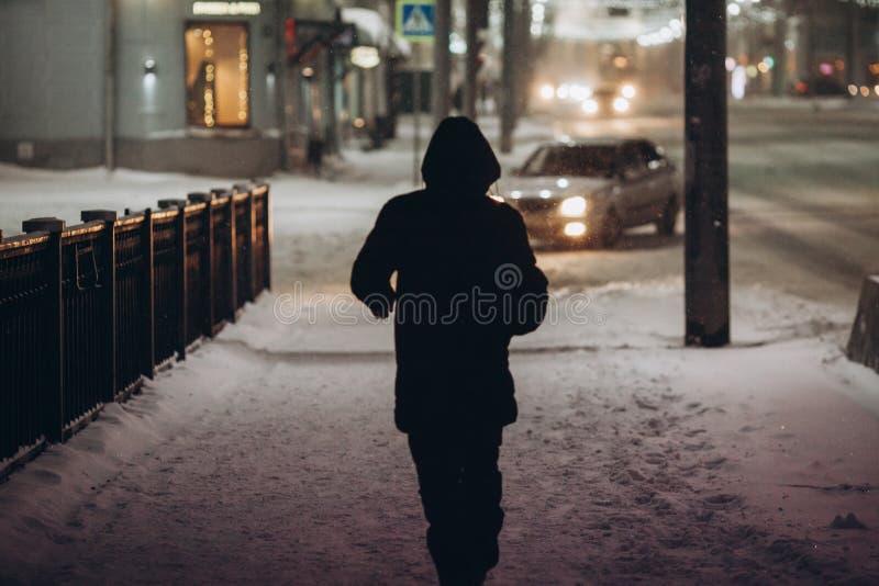 Silhouette d'un homme dans le capot qui descend la rue la nuit dans les chutes de neige photographie stock libre de droits
