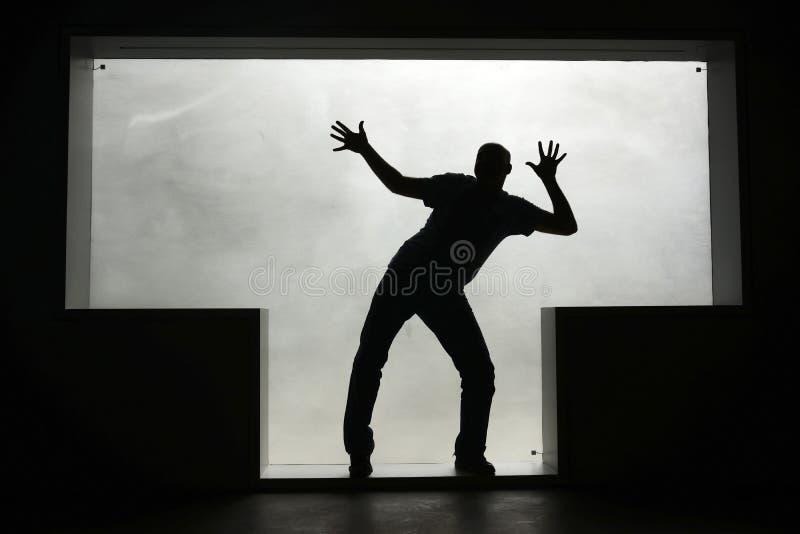 Silhouette d'un homme de danse dans une fenêtre en forme de t image libre de droits