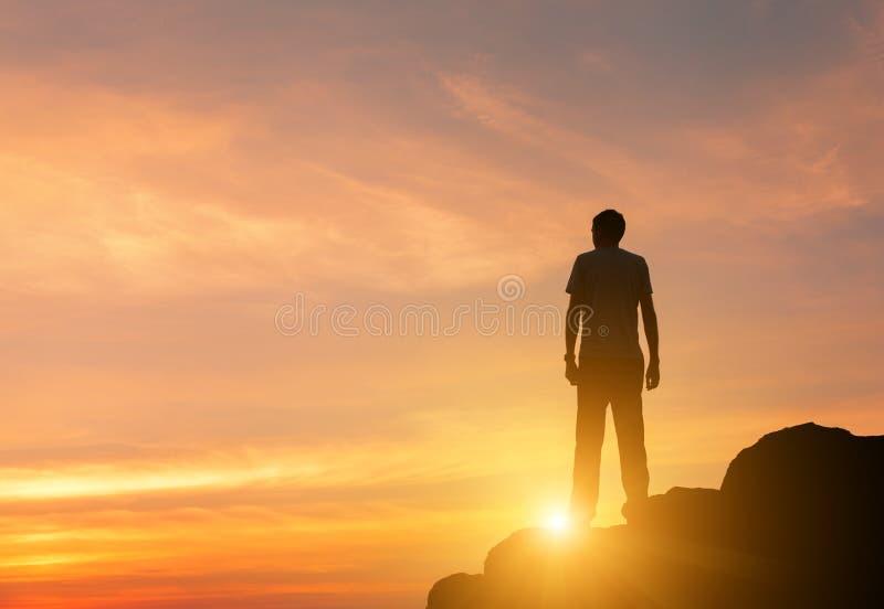 Silhouette d'un homme debout au coucher du soleil coloré en été photo libre de droits