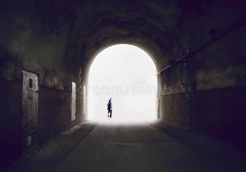 Silhouette d'un homme disparaissant dans la lumière à l'extrémité d'un tunnel images libres de droits