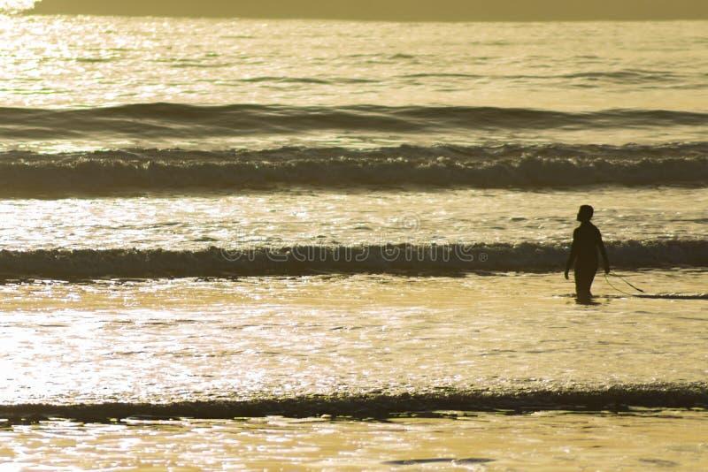 Silhouette d'un homme et de sa planche de surf dans l'Océan Atlantique pendant le coucher du soleil dans Essaouira Maroc photographie stock