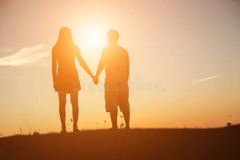 Silhouette d'un homme et d'une femme tenant des mains les uns avec les autres, marchant ensemble image libre de droits