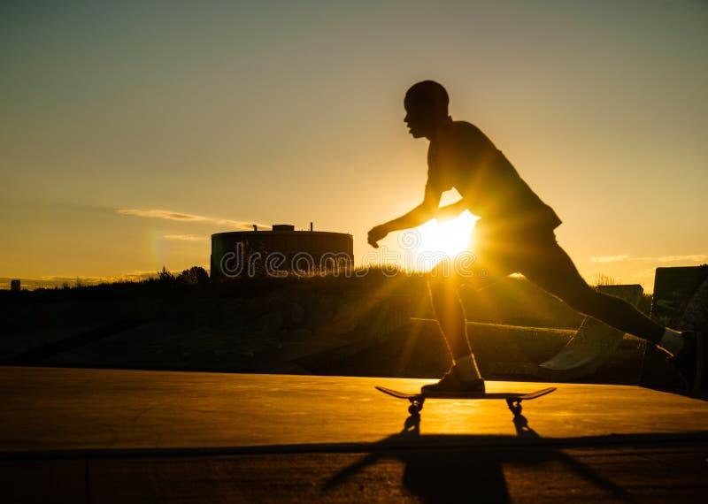 Silhouette d'un homme faisant de la planche à roulettes à un parc public photos libres de droits