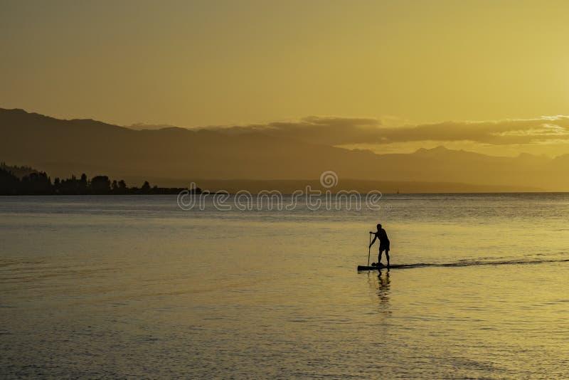 Silhouette d'un homme Paddleboarding dans le rivage au coucher du soleil image stock