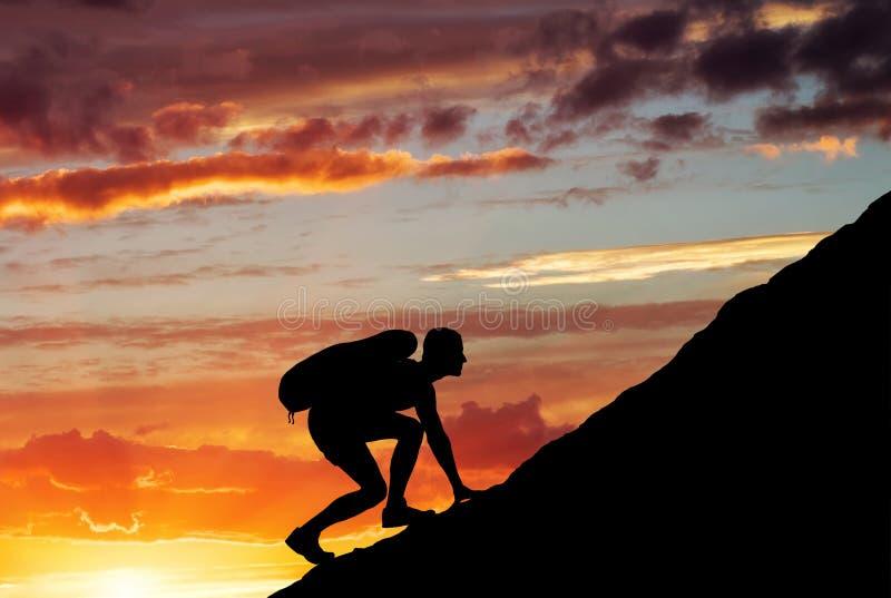 Silhouette d'un homme qui escalade la montagne photos stock