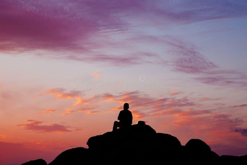 Silhouette d'un homme s'asseyant sur une roche pendant le coucher du soleil image stock