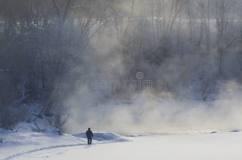 Silhouette d'un homme sur la côte de la rivière congelée avec le brouillard image stock