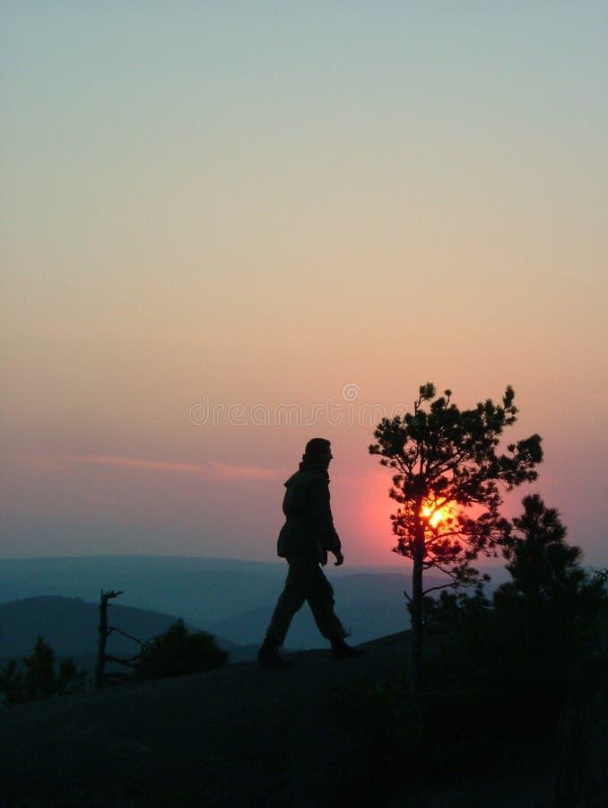 Silhouette d'un homme sur le dessus de montagne au fond de coucher du soleil image libre de droits