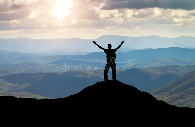 Silhouette d'un homme sur un dessus de montagne photo stock