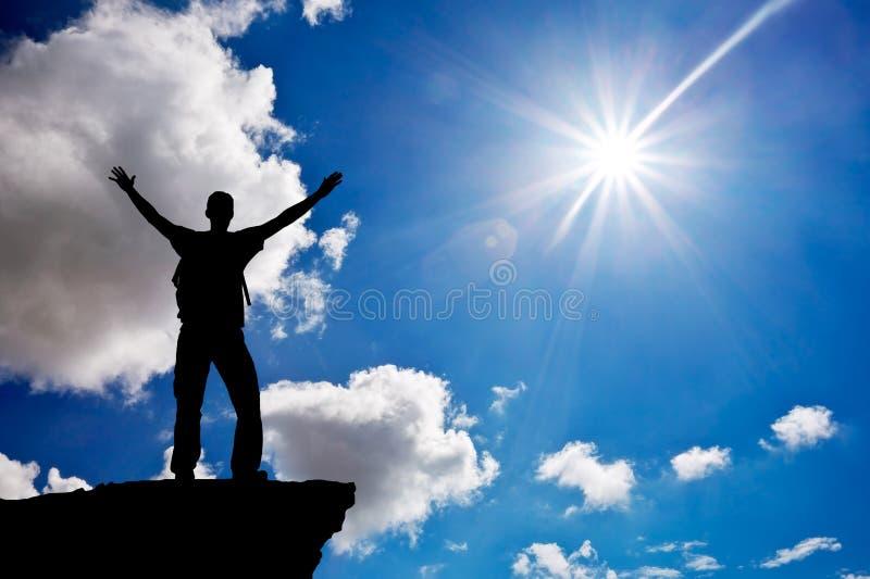 Silhouette d'un homme sur un dessus de montagne Culte à Dieu images stock