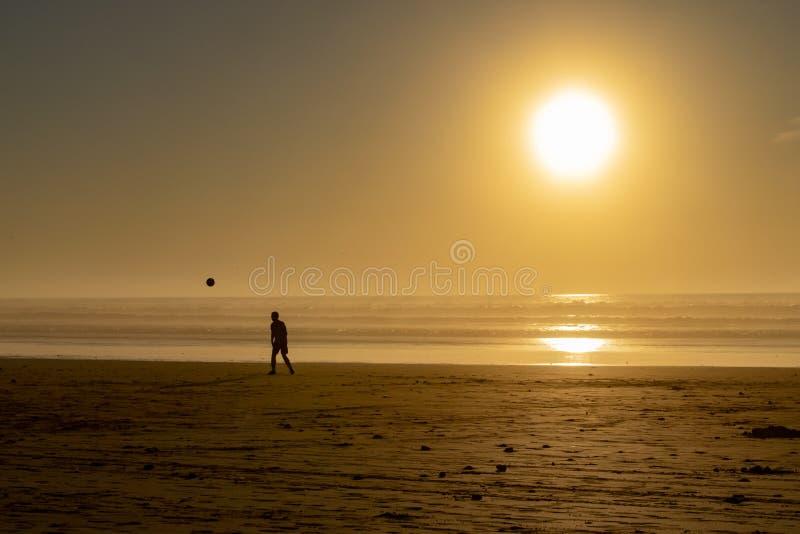 Silhouette d'un homme sur une plage dirigeant un football au coucher du soleil photos stock