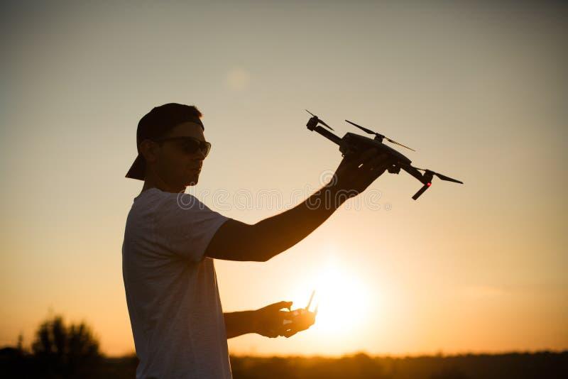 Silhouette d'un homme tenant le petit bourdon compact et le contrôleur à distance dans des ses mains Le pilote lance le quadcopte image stock