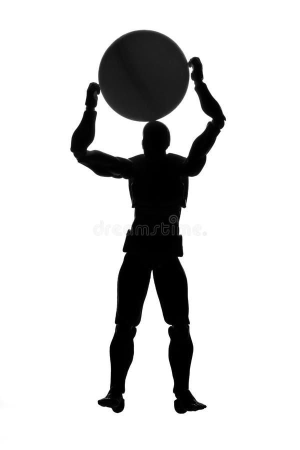 Silhouette d'un homme tenant une boule au-dessus de sa tête images stock
