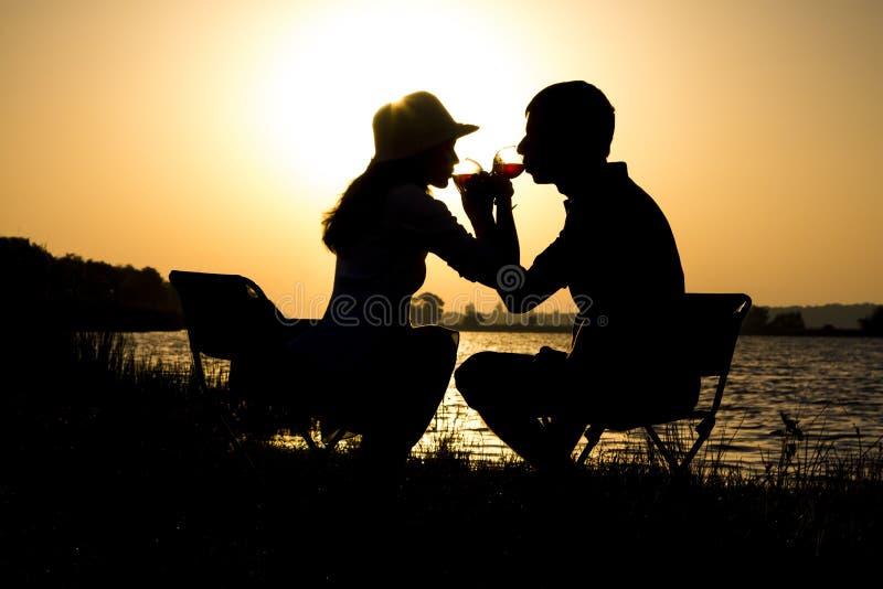 Silhouette d'un jeune couple dans l'amour à partir sur un pique-nique hors de la ville à la fraternité potable de vin d'aube photo stock