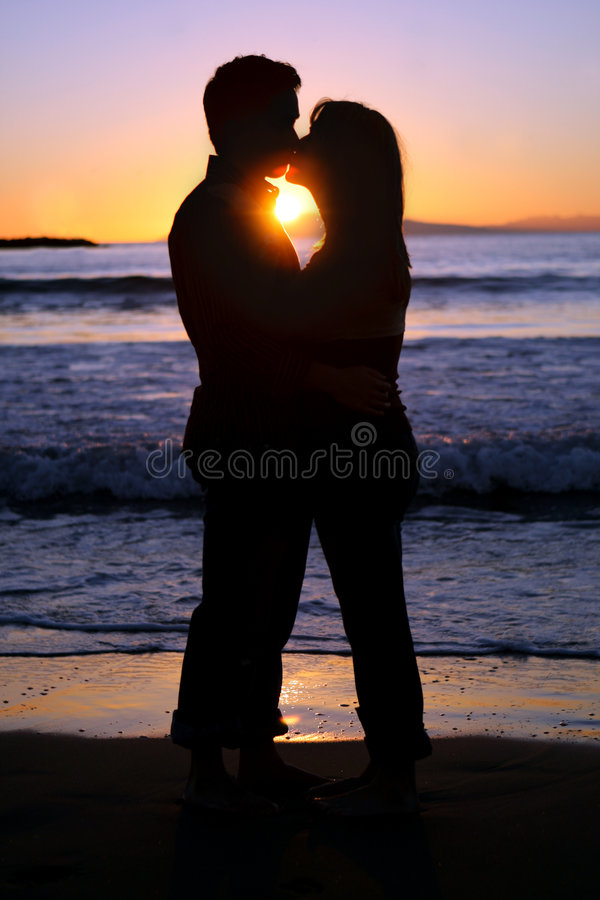 Silhouette d'un jeune couple embrassant à la plage photos stock