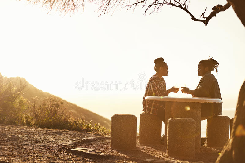 Silhouette d'un jeune couple faisant un pain grillé pendant le coucher du soleil photo libre de droits