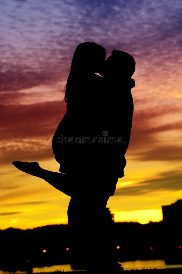 Silhouette d'un jeune couple par l'eau photographie stock libre de droits