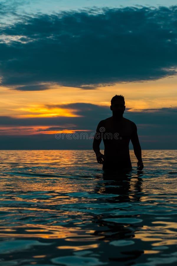 Silhouette d'un jeune homme marchant de la plage photo libre de droits
