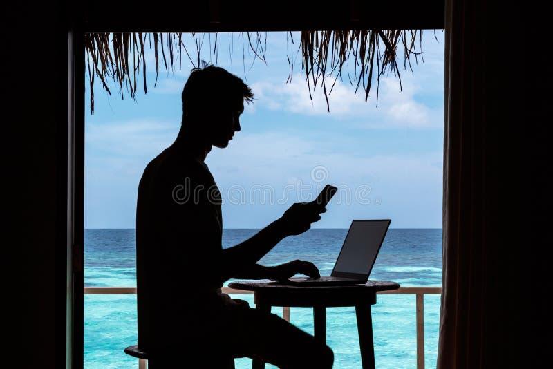 Silhouette d'un jeune homme travaillant avec un ordinateur et un smartphone sur une table L'eau tropicale bleue claire comme fond photos stock