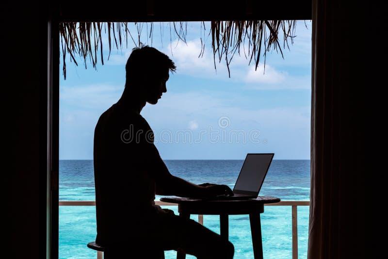 Silhouette d'un jeune homme travaillant avec un ordinateur sur une table L'eau tropicale bleue claire comme fond photos libres de droits