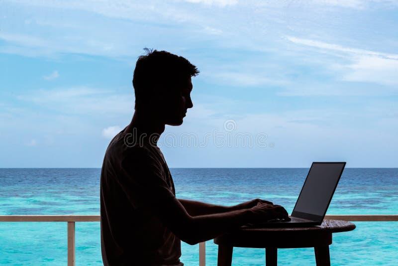 Silhouette d'un jeune homme travaillant avec un ordinateur sur une table L'eau tropicale bleue claire comme fond images stock