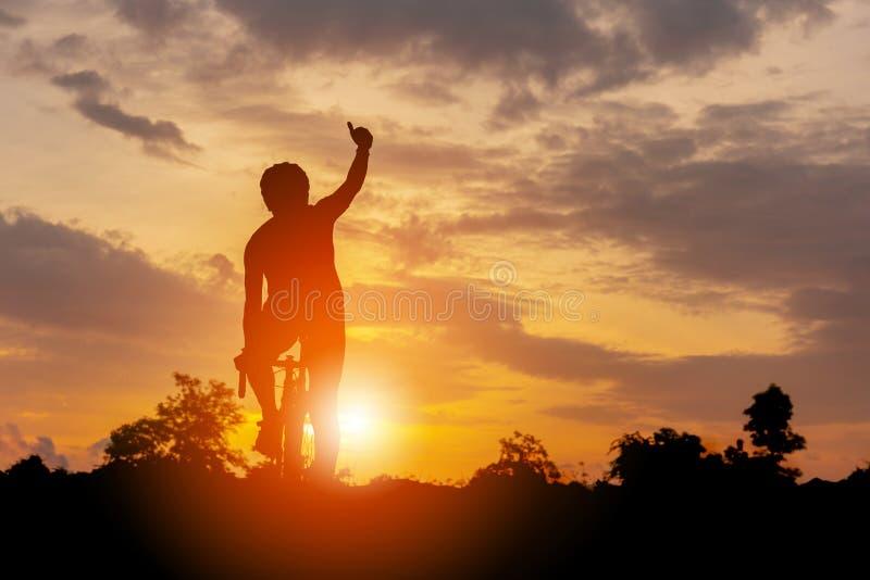 Silhouette d'un mâle de cycliste montant un vélo de route au coucher du soleil, sport photo libre de droits