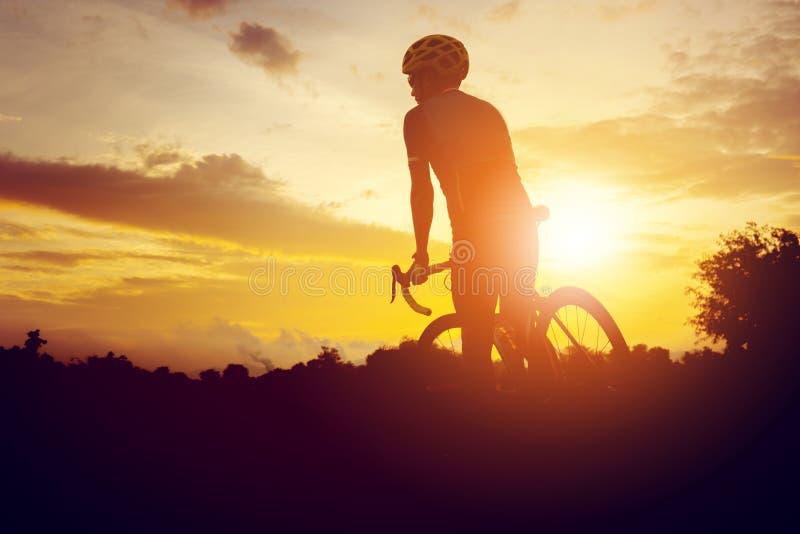 Silhouette d'un mâle de cycliste montant un vélo de route au coucher du soleil, sport images stock