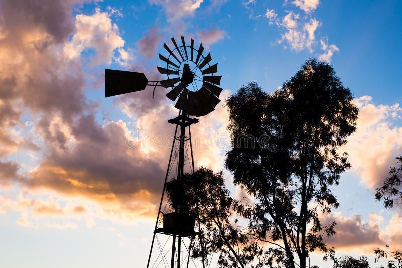 Silhouette d'un moulin à vent fonctionnant de pays de vintage dans la lumière ou le crépuscule de coucher du soleil image stock