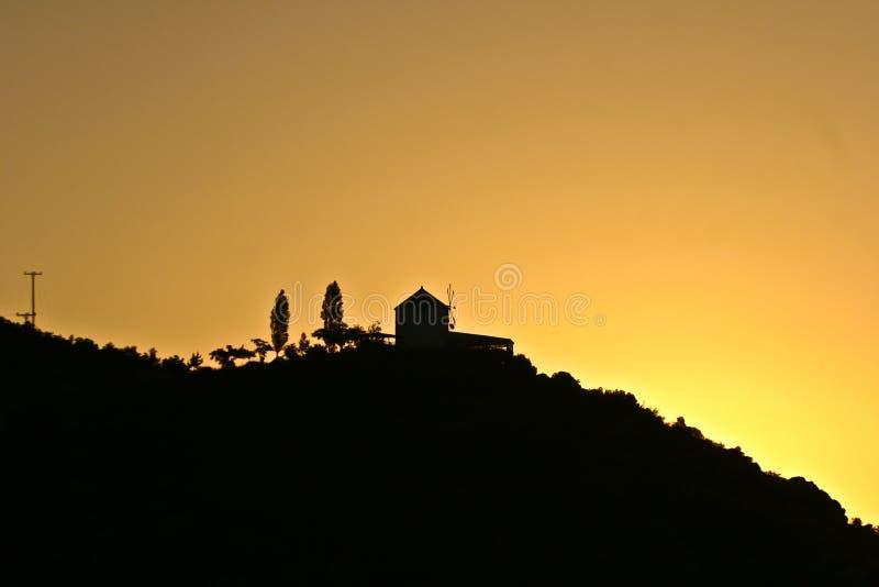 Silhouette d'un moulin de vent dans le coucher du soleil en Grèce images stock