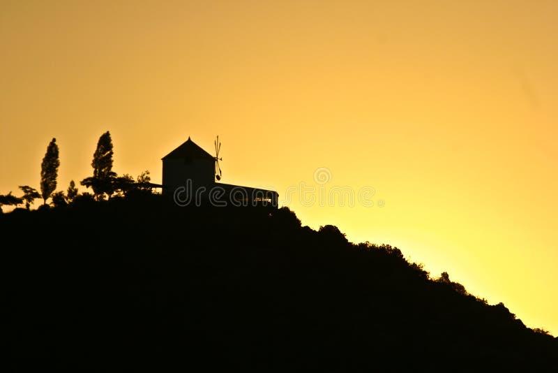 Silhouette d'un moulin de vent dans le coucher du soleil en Grèce photographie stock