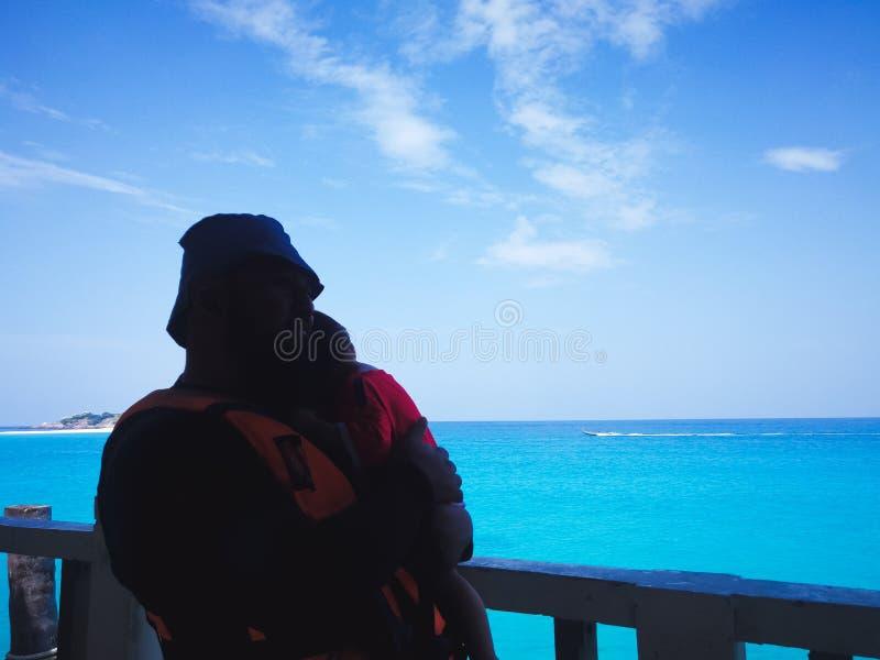 Silhouette d'un petit enfant avec son père sur la plage pendant la journée, concept de la famille image libre de droits