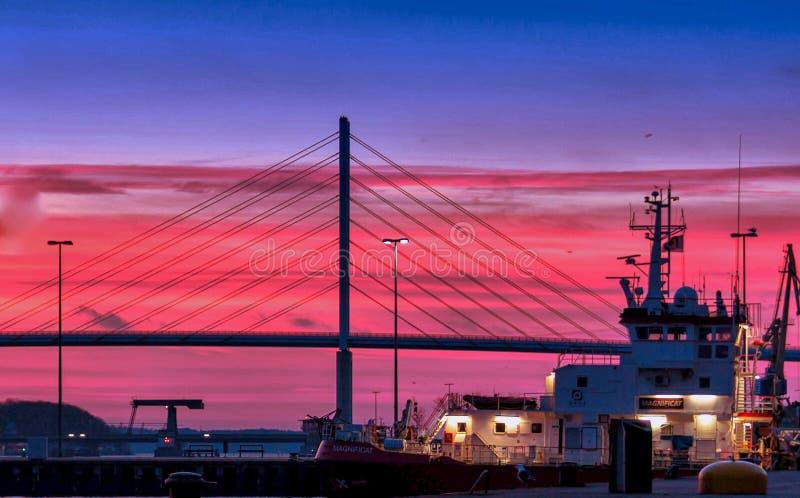 Silhouette d'un pont sous les nuages rouges et le ciel bleu prise pendant la nuit photo stock