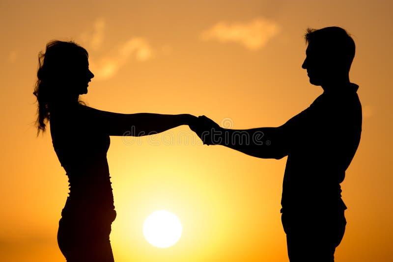 Silhouette d'un type et d'une fille au coucher du soleil photo stock