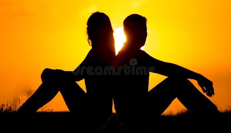 Silhouette d'un type et d'une fille au coucher du soleil images libres de droits