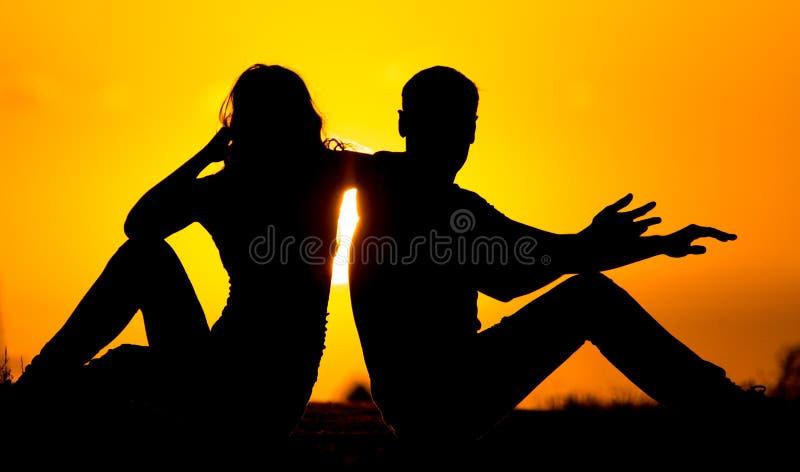Silhouette d'un type et d'une fille au coucher du soleil photos stock