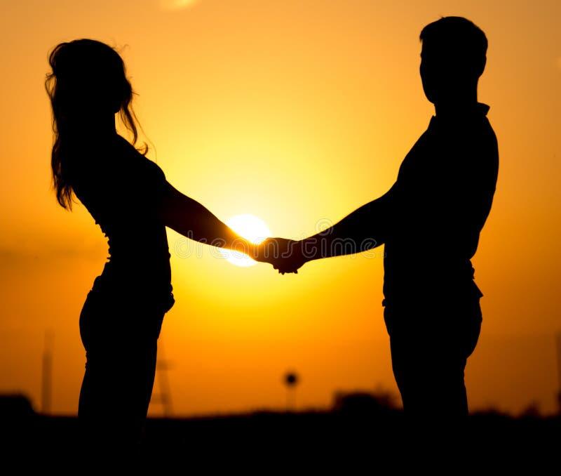 Silhouette d'un type et d'une fille au coucher du soleil photographie stock libre de droits